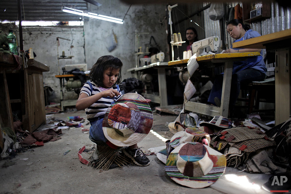 In this March 25, 2016 photo, Nepalese earthquake amputee victim Nirmala Pariyar, 8, helps her father at a textile factory in Kathmandu, Nepal. (AP Photo/Niranjan Shrestha)