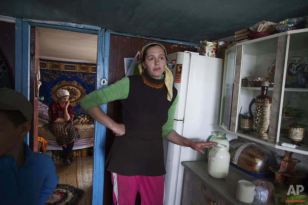 In this photo taken on Tuesday, April  5, 2016, Viktoria Vetrova holds a jar with fresh cow milk, believed to be radioactive, in her house, with her mother Tatiana Vetrova sitting in the back, in Zalyshany, 53 km (32 miles) southwest of the destroyed reactor of the Chernobyl plant, Ukraine. Viktoria Vetrova, a housewife, keeps two cows in order to help feed her four children. Her village is in one of the sections of Ukraine contaminated by radioactive fallout from the Chernobyl nuclear explosion. (AP Photo/Mstyslav Chernov)