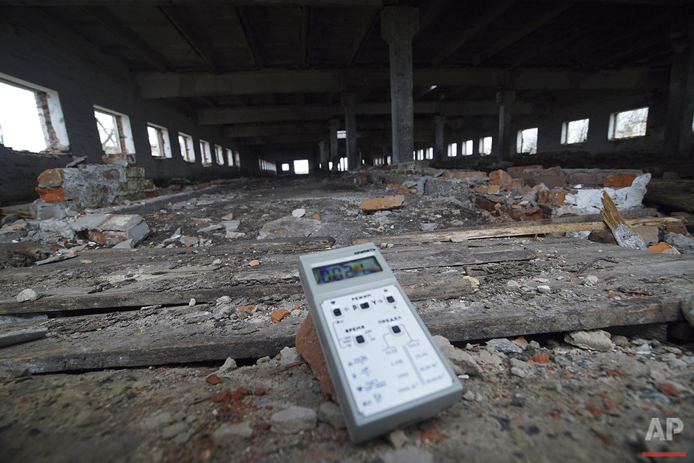 In this photo taken on Thursday, April  7, 2016, a radiation dosimeter measures radiation showing slightly increased levels in an abandoned cow farm near Zalyshany, Ukraine. After the April 26, 1986 explosion and fire spewed radioactive fallout over much of Ukraine, the most heavily affected areas were classified into four zones. Zalyshany, 53 kilometers (32 miles) southwest of the destroyed reactor, is in the fourth zone, not contaminated enough for resettlement but eligible for subsidies to help with health issues. (AP Photo/Mstyslav Chernov)