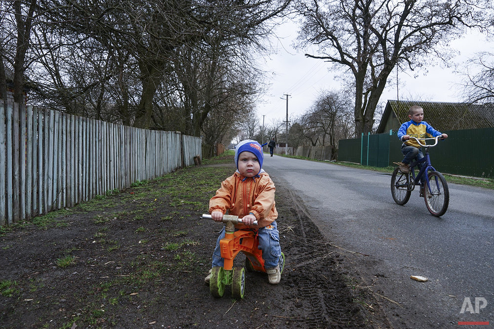 In this photo taken on Thursday, April  7, 2016, children ride bicycles in the village of Pysky, Ukraine. After the April 26, 1986 explosion and fire spewed radioactive fallout over much of Ukraine, the most heavily affected areas were classified into four zones, from three of which residents were evacuated or allowed to volunteer for resettlement.  (AP Photo/Mstyslav Chernov)