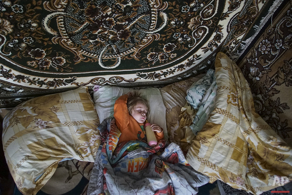 In this photo taken on Tuesday, April  5, 2016, Natalya Vetrova, one-years-old, sleeps holding a bottle with fresh cow milk at home in Zalyshany, 53 km (32 miles) southwest of the destroyed reactor of the Chernobyl plant, Ukraine. Her village is in one of the sections of Ukraine contaminated by radioactive fallout from the Chernobyl nuclear explosion. (AP Photo/Mstyslav Chernov)