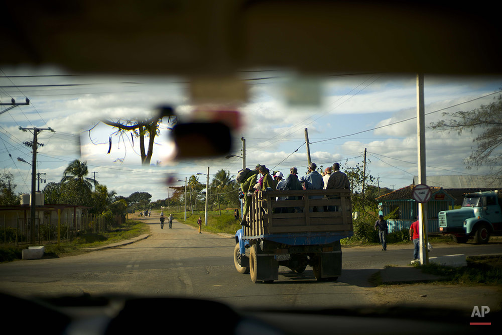 In this Feb. 26, 2016 photo, a soldier climbs up a truck that stopped for him to join residents commuting home after the workday in the province of Pinar del Rio, Cuba, where tobacco farming is the main crop. Despite the flood of visitors since Cuba and the U.S. reestablished relations, some aspects of life in the province's central Vinales valley have changed little. (AP Photo/Ramon Espinosa)