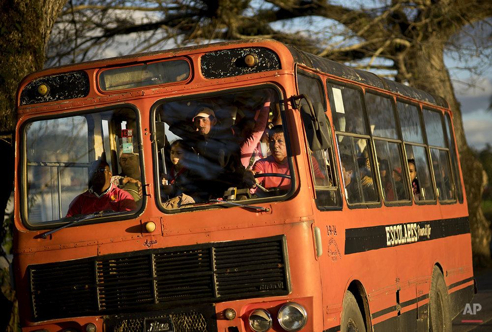 In this Feb. 26, 2016 photo, residents travel in a former school bus to the center of the town of Vinales in the province of Pinar del Rio, Cuba, where tobacco farming is the main crop. Despite the flood of visitors since Cuba and the U.S. reestablished relations, some aspects of life in the province's central Vinales valley have changed little. (AP Photo/Ramon Espinosa)