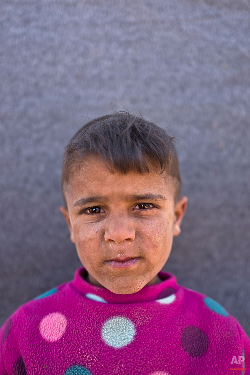 "In this Friday, March 11, 2016 photo, Syrian refugee boy Omar Suliman, 5, from Hassakeh, Syria, poses for a picture at an informal tented settlement near the Syrian border on the outskirts of Mafraq, Jordan. "" I want to grow up"" Omar said.  About half of the 4.8 million Syrians who fled their homeland are children, and some of the most vulnerable live in dozens of makeshift tent camps, including Jordan, which has taken in close to 640,000 refugees. (AP Photo/Muhammed Muheisen)"