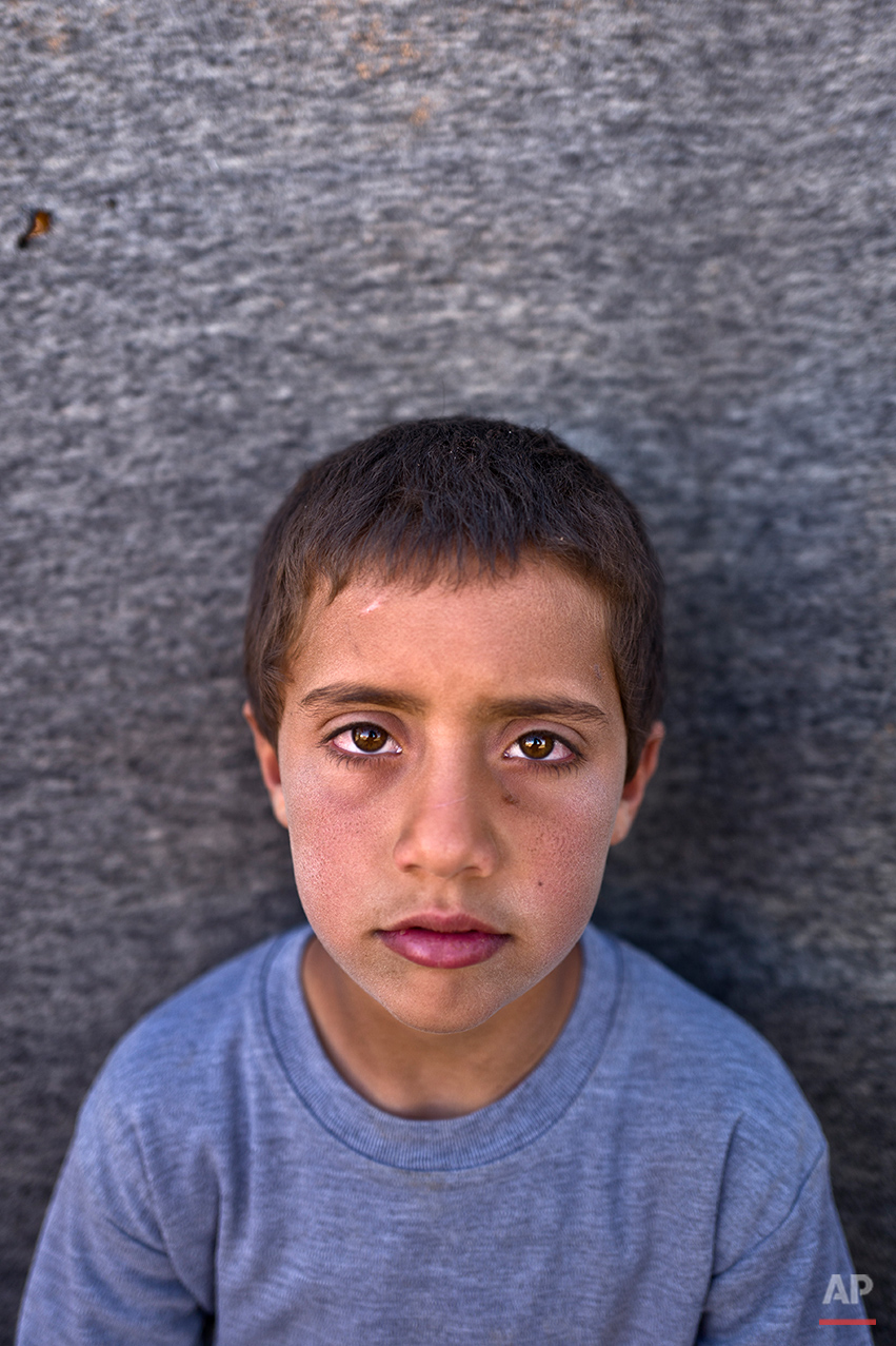 "In this Monday, March 14, 2016 photo, Syrian refugee boy Khalid Rakan, 10, from Hama, Syria, poses for a picture at an informal tented settlement near the Syrian border on the outskirts of Mafraq, Jordan. ""I just want to go back to our home in Syria"" Khalid said.  About half of the 4.8 million Syrians who fled their homeland are children, and some of the most vulnerable live in dozens of makeshift tent camps, including Jordan, which has taken in close to 640,000 refugees. Children in these camps near the northern city of Mafraq say they miss their old lives in Syria, especially going to school. (AP Photo/Muhammed Muheisen)"