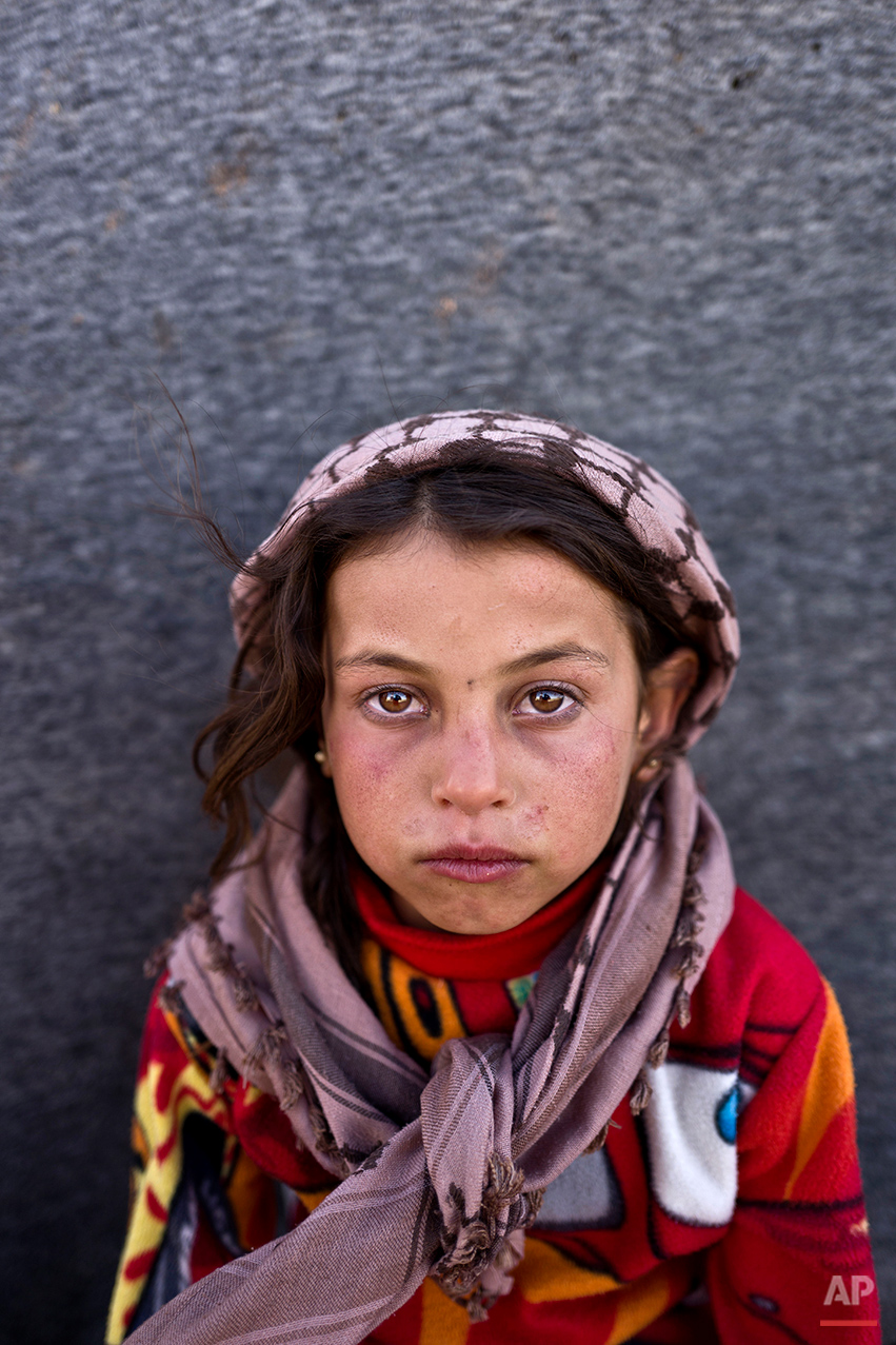 In this Monday, March 14, 2016 photo, Syrian refugee girl  Hanan Khalid, 7, from Hassakeh, Syria, poses for a picture at an informal tented settlement near the Syrian border on the outskirts of Mafraq, Jordan. The conflict, which entered its sixth year this week, has killed more than 250,000 people in Syria and displaced close to half the pre-war population of 23 million. Children in these camps near the northern Jordanian city of Mafraq say they miss their old lives in Syria, especially going to school. (AP Photo/Muhammed Muheisen)