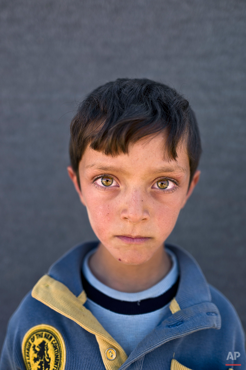 "In this Friday, March 11, 2016 photo, Syrian refugee boy Ahmad Zughayar, 6, from Deir el-Zour, Syria, poses for a picture at an informal tented settlement near the Syrian border on the outskirts of Mafraq, Jordan. ""I remember the sound of bombings on homes in Deir el-Zour,"" says Zughayar. (AP Photo/Muhammed Muheisen)"