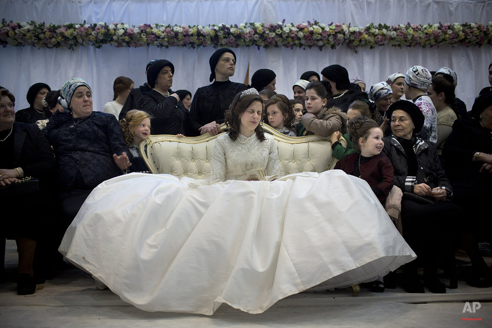 A Jewish bride sits with family members in the women's section during her wedding to the grandson of the Rabbi of the Tzanz Hasidic dynasty community, in Netanya, Israel, Tuesday, March 15, 2016. (AP Photo/Oded Balilty)