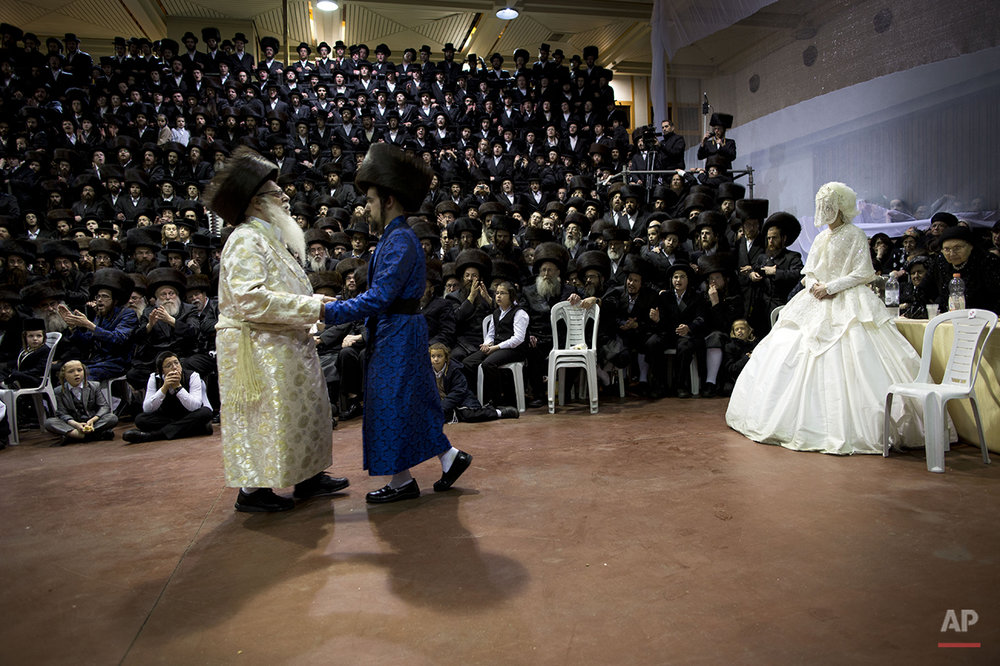 An ultra-Orthodox Jewish bride enters to the men's section of the wedding, to fulfill the Mitzvah tantz, in which family members and honored rabbis are invited to dance in front of the bride, often holding a gartel, and then dancing with the groom, during her wedding to the grandson of the Rabbi of the Tzanz Hasidic dynasty community, in Netanya, Israel,in Netanya, Israel, Wednesday, March 16, 2016. (AP Photo/Oded Balilty)