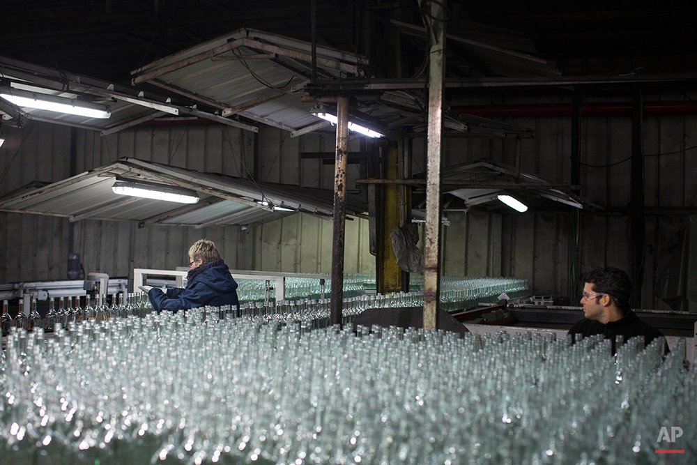 In this Wednesday, Jan. 27, 2016 photo, glass bottles move on the production line at the Phoenicia Glass Works Ltd. factory in the southern Israeli town of Yeruham. Factory workers grind these rejects into shards and pile them outside. Recycled glass bottles from across the country are sent here and ground up, too. The glass pieces are shoveled into the ovens to be fired into new glass bottles. Sand, the basic ingredient of glass, is hauled in from a nearby desert quarry. (AP Photo/Oded Balilty)