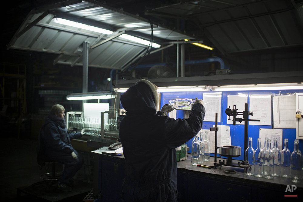 In this Wednesday, Jan. 27, 2016 photo, an employee checks the quality of glass bottles on the production line at Phoenicia Glass Works Ltd. factory in the southern Israeli town of Yeruham. Phoenicia Glass Works, Israel's only glass container factory, produces one million containers a day. Some 300,000 bottles a day come out with defects, and the factory grinds them into shards and piles them in a desert lot to be melted into new bottles. The factory is in the middle of the desert, and works round the clock, every day of the year. (AP Photo/Oded Balilty)