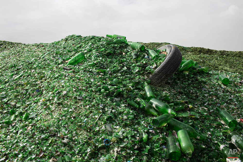 In this Sunday, Jan. 24, 2016 photo, broken glass bottles later to be recycled at the Phoenicia Glass Works Ltd. factory in the southern Israeli town of Yeruham. Tiny shards, millions of them, are piled into rolling hills of green and brown. They are 50 feet high and span the length of a few soccer fields. This is the junkyard at Israel's only glass container factory, where broken glass awaits a new life. (AP Photo/Oded Balilty)