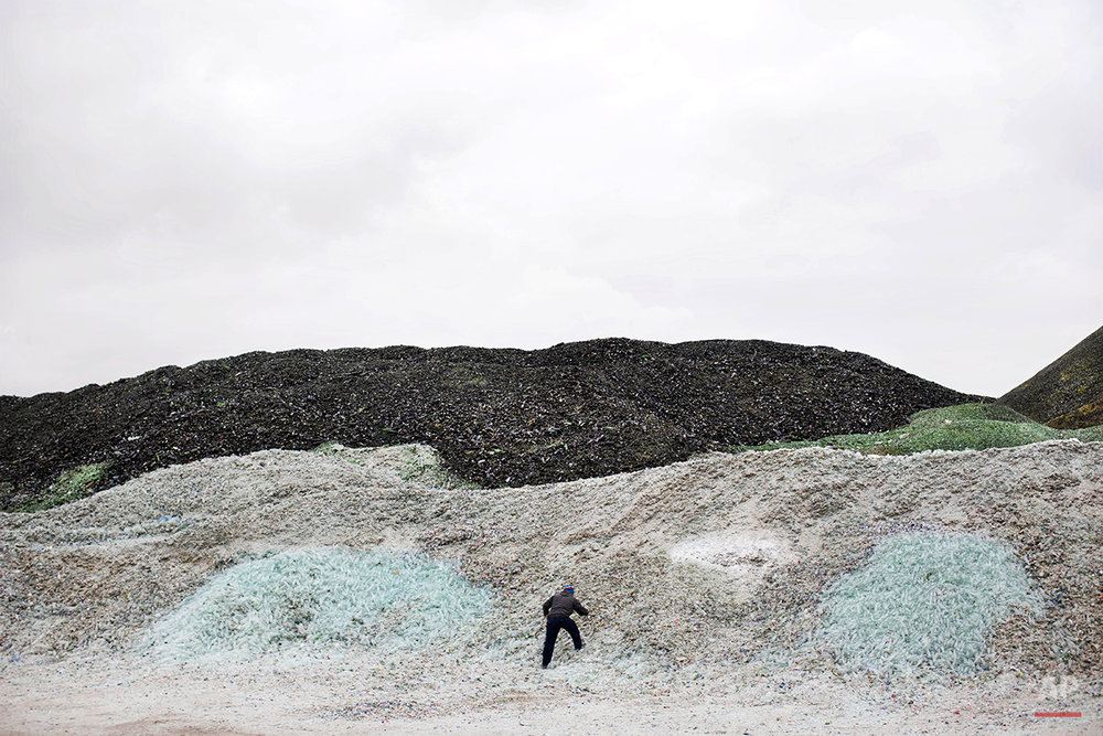 In this Wednesday, Jan. 27, 2016 photo, a worker collects plastic bottles among piles of broken glass, later to be recycled at the Phoenicia Glass Works Ltd. factory in the southern Israeli town of Yeruham. Phoenicia Glass Works Ltd., Israel's only glass container factory, produces one million containers a day. Some 300,000 bottles a day come out with defects, and the factory grinds them into shards and piles them in a desert lot to be melted into new bottles. The factory is in the middle of the desert, and works round the clock, every day of the year. (AP Photo/Oded Balilty)