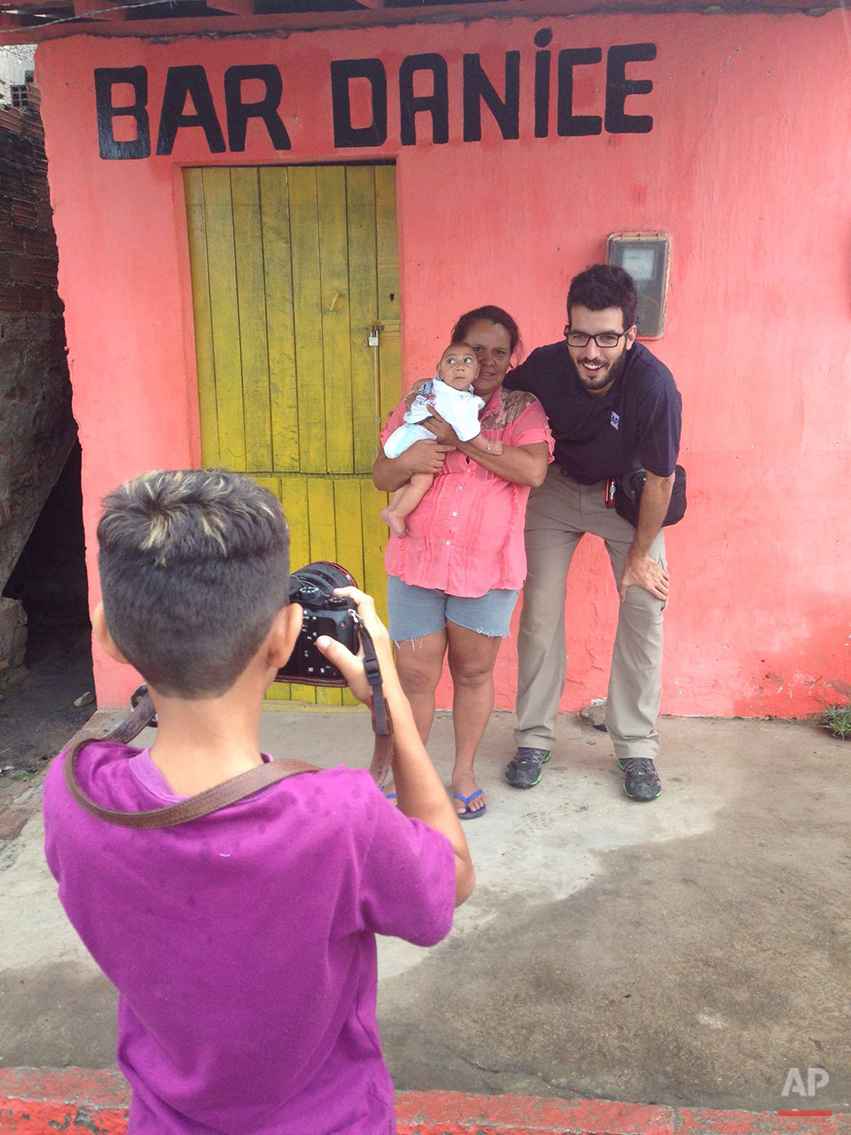In this  Jan. 30, 2016 photo, Associated Press photographer Felipe Dana poses for a photo with Solange Ferreira holding her son Jose Wesley, who suffers from microcephaly, a kind of brain deformity in babies, in Bonito, Pernambuco state, Brazil, as Solange's other son Elison takes their picture. Dana returned to document the lives of Ferreira's family after first meeting them in December 2015 at a hospital. Brazil's health officials say they're convinced the jump in the number of babies born with microcephaly is linked to a sudden outbreak of the Zika virus.  (AP Photo/Mario Lobao)