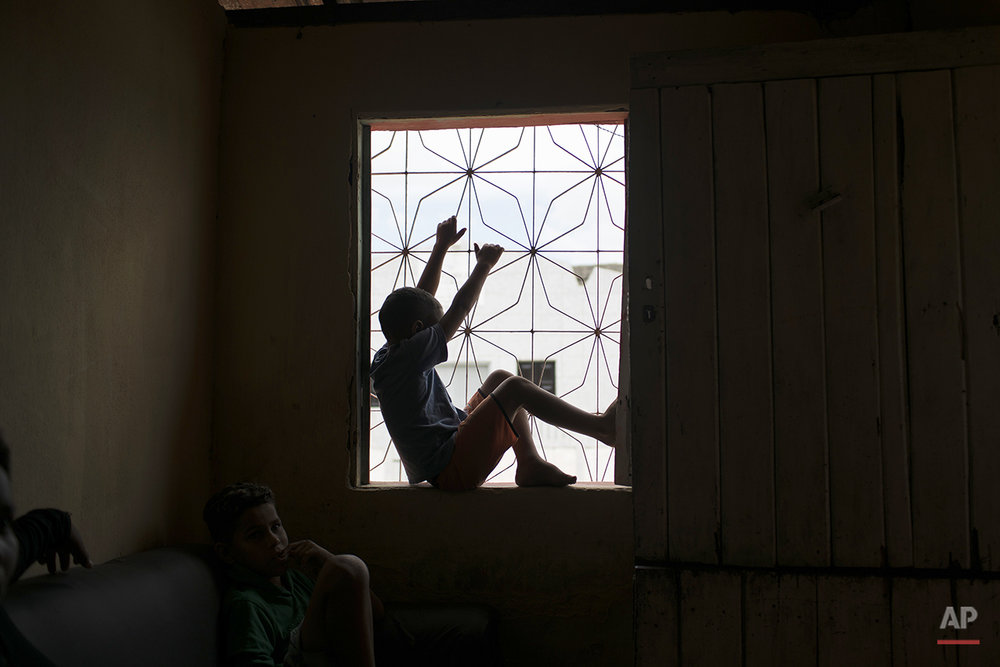 """In this Jan. 30, 2016 photo, Jose Wesley's older brother Elenilson plays inside of their house in Bonito, Pernambuco state, Brazil. His mother Solange Ferreira cried when she said she had realized that her youngest son Jose Wesley, who was born with microcephaly, may never run and play like her two older children. """"Now I have started believing that it is actually the other babies that have heads that are too big,"""" she said, in a tone both playful and sad. """"Jose is my new normal."""" (AP Photo/Felipe Dana)"""