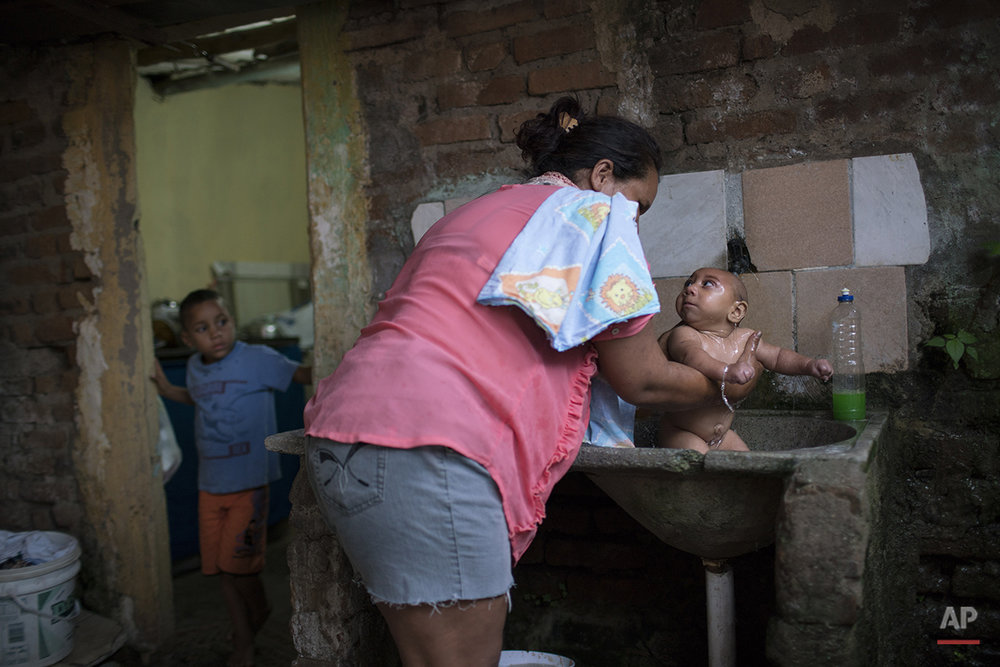 In this Jan. 30, 2016 photo, Solange Ferreira bathes Jose Wesley in a sink in their house in Bonito, Pernambuco state, Brazil. The town of Bonito is no different than others in terms of mosquitoes and the viruses they transmit, such as Zika, dengue and chikungunya. (AP Photo/Felipe Dana)