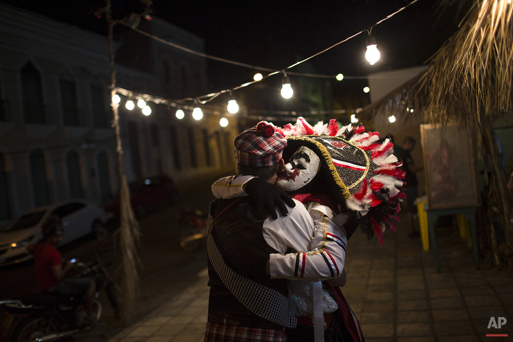 "A ""Careta"" embraces a reveler during Carnival in Triunfo, Brazil, Monday, Feb. 8, 2016. Residents in this small town say the Careta tradition began after two men were forbidden to take part in a folk celebration due to their drunken behavior. As retaliation, the pair roamed the streets wearing masks painted with sour expressions. Every Carnival since then, ""Caretas' groups parade through Triunfo wearing their dour masks and cracking whips. (AP Photo/Felipe Dana)"