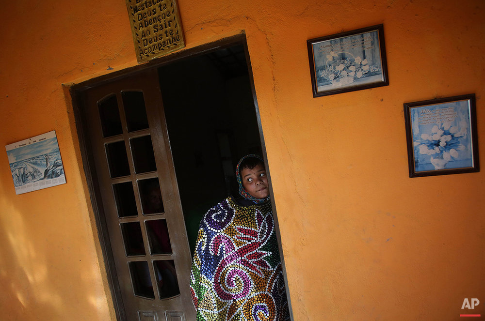 In this Feb. 7, 2016 photo, a youth leaves his home wearing a costume as he heads to the Maracatu Carnival celebrations in Nazare da Mata, Brazil. During Carnival, all of Nazare de la Mata mobilizes in maracatu groups, dressing up in colorful costumes and large headdresses. (AP Photo/Eraldo Peres)