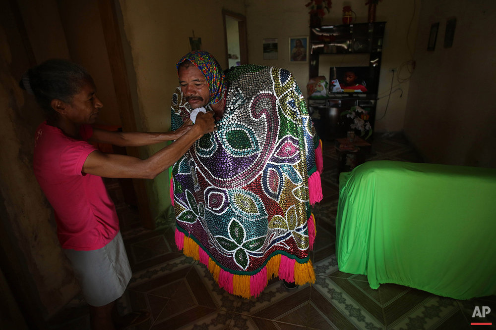 """In this Feb. 7, 2016 photo, a man gets help with his """"Caboclo de Lanca"""" costume, at home ahead of Maracatu Carnival celebrations in Nazare da Mata, Brazil. The Carnival's main character is """"Caboclo de Lanca,"""" a lance-bearer wearing a huge, embroidered cape. (AP Photo/Eraldo Peres)"""