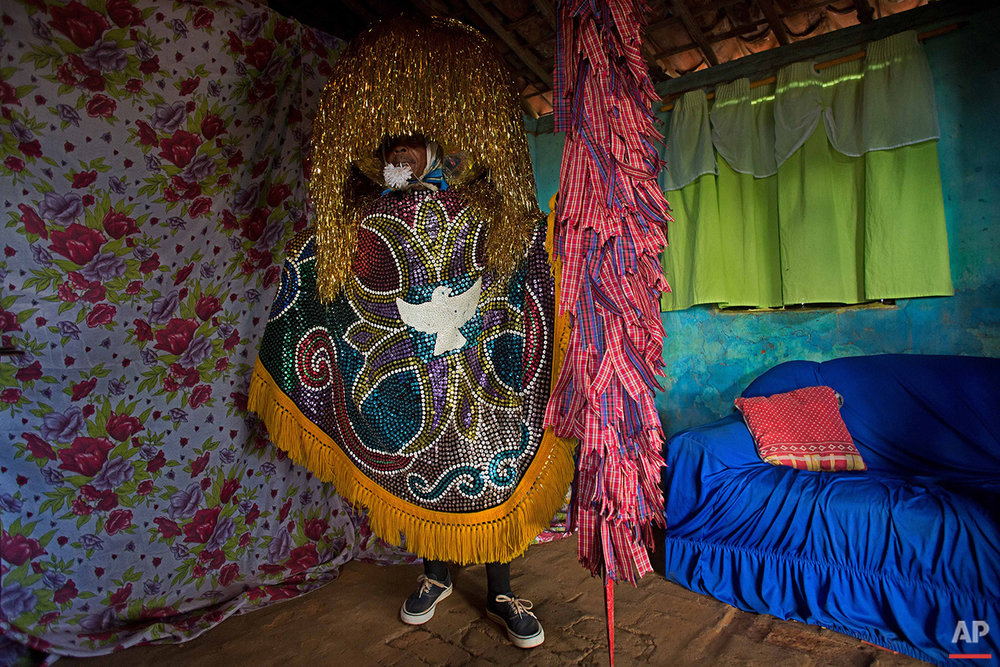"""In this Feb. 2, 2016 photo, Jose Esteves, a """"Caboclo de Lanca,"""" or lance-bearer, wears his costume before performing at the Maracatu Carnival in Nazare da Mata, Brazil. This city in northern Brazil is considered the cradle of the maracatu, a frenetic, rhythmic dance of African origin that infuses its unique Carnival celebration with its spirit. (AP Photo/Eraldo Peres)"""