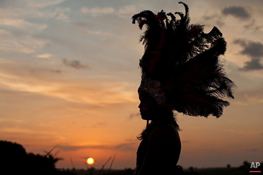 In this Jan. 27, 2016 photo, a girl wears a feathered headdress as she prepares for Maracatu Carnival festivities in Nazare da Mata, Brazil. The Afro-indigenous tradition dates back centuries and arose from the mixing of the faiths of slaves with local indigenous customs. (AP Photo/Eraldo Peres)