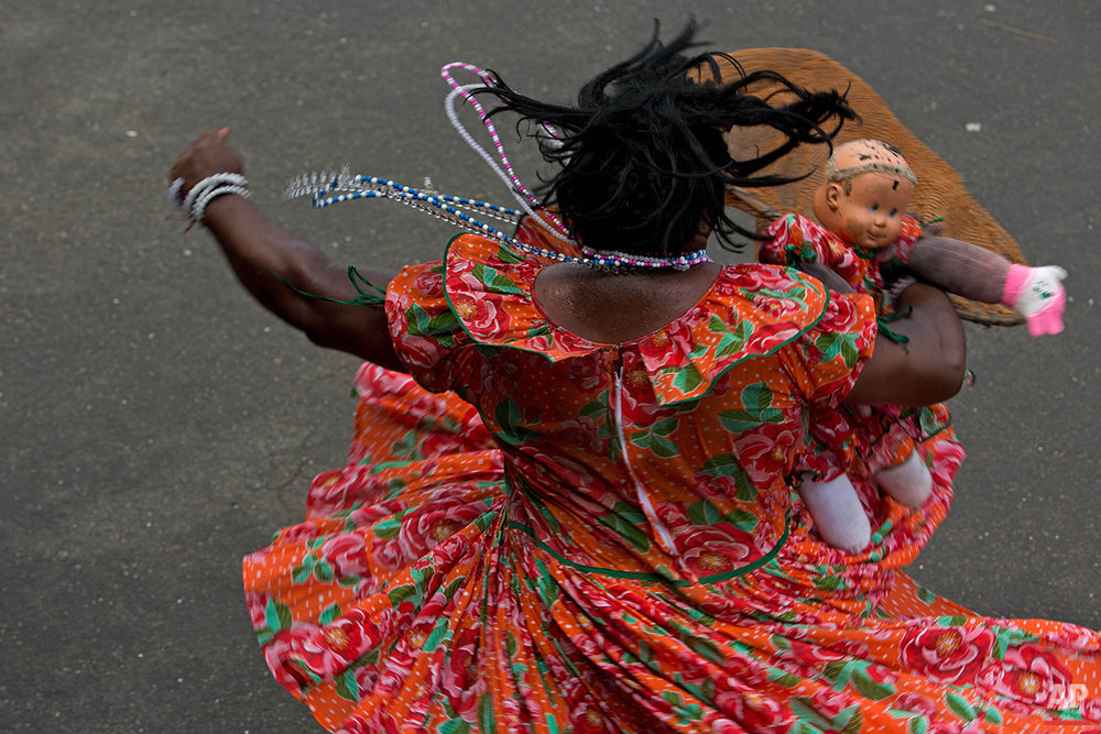 """In this Feb. 8, 2016 photo, a person dressed as the character """"Catita Daiana,"""" dances at Maracatu Carnival celebrations in Nazare da Mata, Brazil. The Afro-indigenous tradition dates back centuries and arose from the mixing of the faiths of slaves brought to work on the local sugar plantations with local indigenous customs. (AP Photo/Eraldo Peres)"""