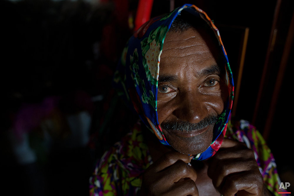 In this Jan. 26, 2016 photo, Antonio Esteves gets into costume for Maracatu Carnival celebrations in Nazare da Mata, Brazil. The Afro-indigenous tradition dates back centuries and arose from the mixing of the faiths of slaves brought to work on the local sugar plantations with local indigenous customs. (AP Photo/Eraldo Peres)
