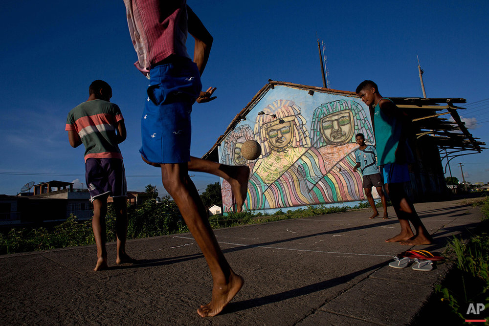 In this Feb. 5, 2016 photo, youth play soccer near a mural featuring traditional characters from Maracatu Carnival in Nazare da Mata, Brazil. This city in northern Brazil is considered the cradle of the maracatu, a frenetic, rhythmic dance of African origin that infuses its unique Carnival celebration with its spirit. (AP Photo/Eraldo Peres)