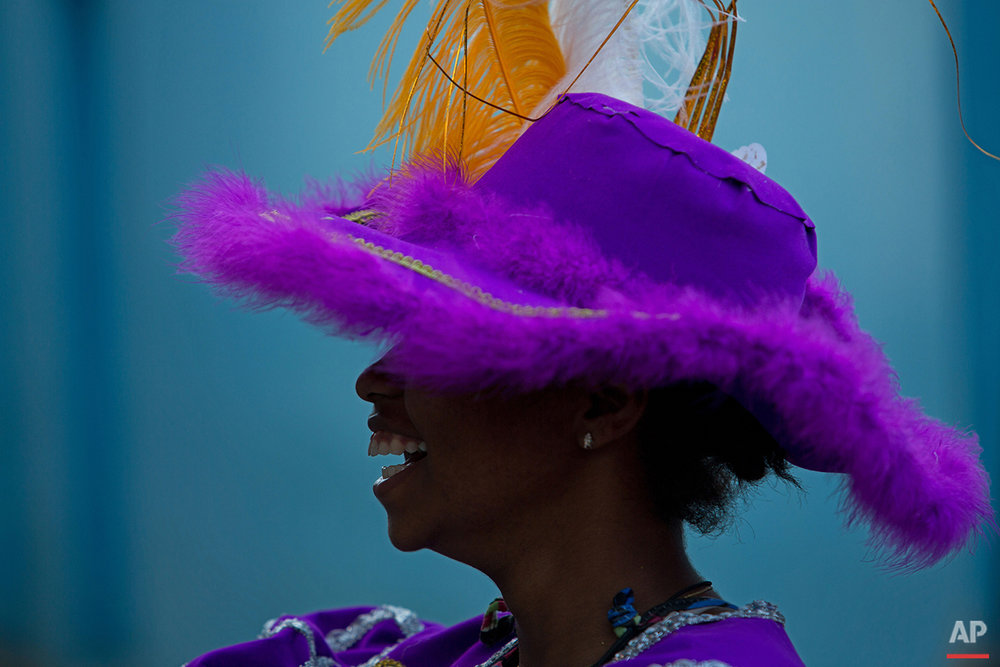 """In this Feb. 8, 2016 photo, a woman dressed up as the traditional character """"Baiana"""" attends Maracatu Carnival celebrations in Nazare da Mata, Brazil. The Afro-indigenous tradition dates back centuries and arose from the mixing of the faiths of slaves brought to work on the local sugar plantations with local indigenous customs. (AP Photo/Eraldo Peres)"""