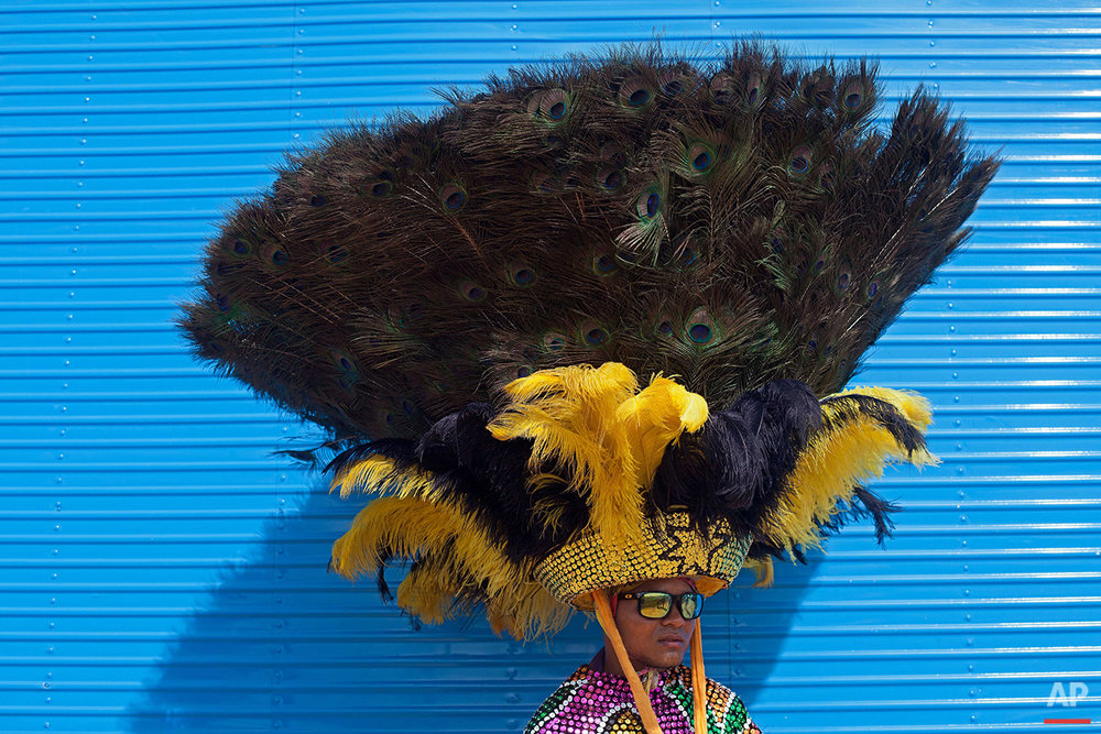 """In this Feb. 7, 2016 photo, a person dressed as the character """"Arreiama"""" wears a feathered headdress at the Maracatu Carnival in Nazare da Mata, Brazil. Participants go from house to house asking for food and drink, a tradition that began long ago with people traveling between the region's sugar plantations. (AP Photo/Eraldo Peres)"""