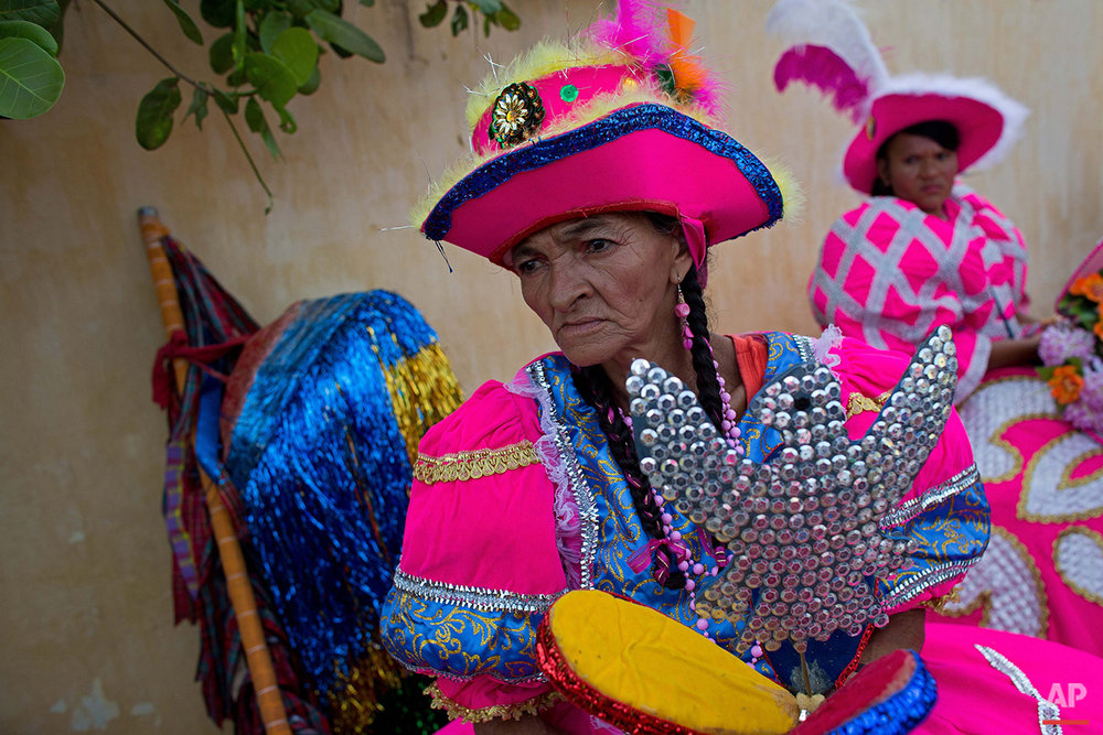 """In this Jan. 26, 2016 photo, a woman dressed as the """"Baianas"""" character waits in costume for the Maracatu Carnival celebrations to start in Nazare da Mata, Brazil. Maracatu dancers gathered in the town's main plaza, converging from across the city and surrounding rural areas. (AP Photo/Eraldo Peres)"""