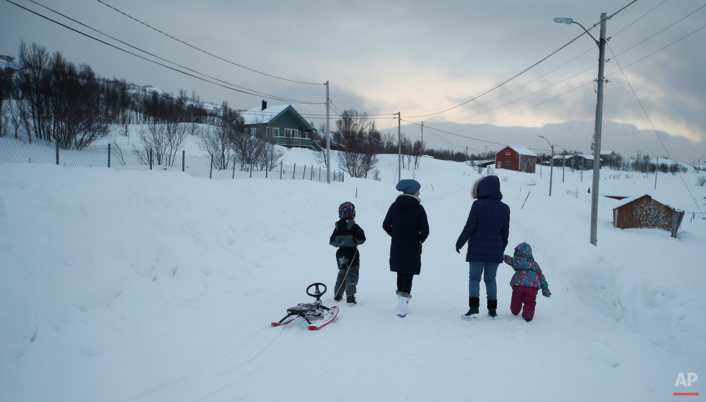 in this photo taken Tuesday, Feb. 2, 2016, asylum seekers take their children for a walk near the temporary accommodation at  the Altnes camp on the island of Seiland, northern Norway. (AP Photo/Alastair Grant)