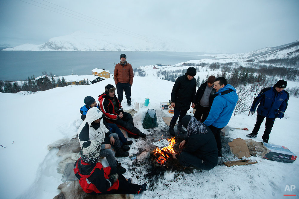 In this photo taken Tuesday, Feb. 2, 2016, asylum seekers gather around a fire as they cook a meal overlooking the temporary Altnes refugee camp on the island of Seiland, northern Norway. Waiting for their asylum claims to be processed, hundreds of people in emergency shelters in Hammerfest and neighboring towns are slowly getting used to the extreme climate and unfamiliar customs of the High North. They say they have adapted to the cold _ the temperature rarely drops below minus 10 degrees C (14 F) along the coast, though it gets much colder further inland. It's the darkness that throws them off. (AP Photo/Alastair Grant)