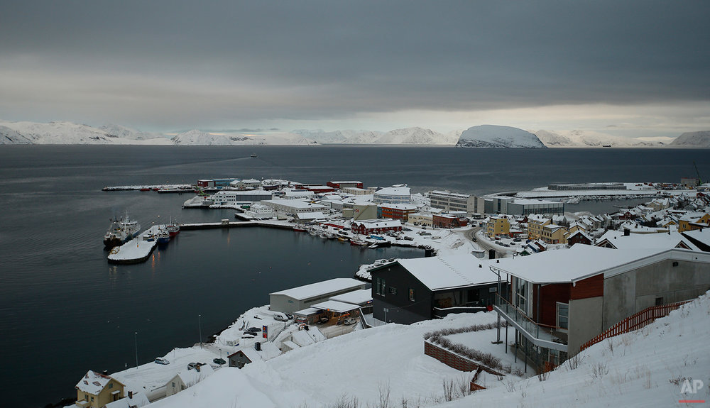 In this photo taken Thursday Feb. 4, 2016, showing a general view of Hammerfest, northern Norway, with a view over the town and the refugee camp, top right. After hiding below the horizon for two long months, the sun has finally risen in Hammerfest, casting a pale pink hue over the Arctic landscape surrounding the world's northernmost refugee shelter. (AP Photo/Alastair Grant)