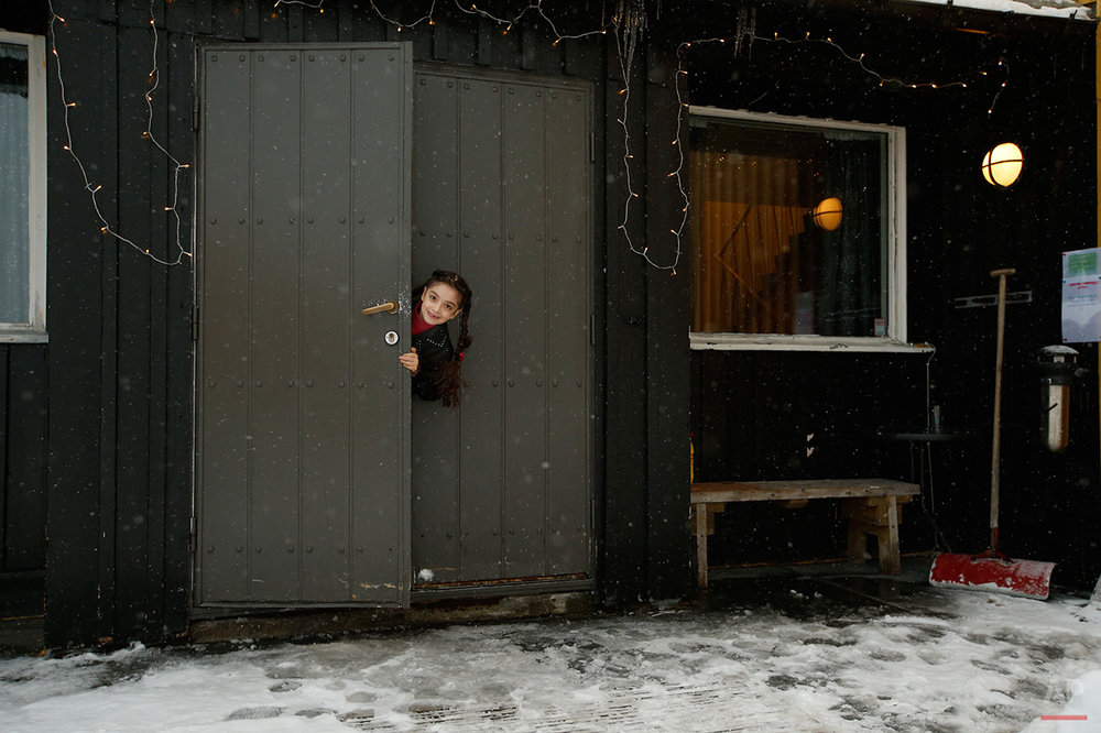 In this photo taken Tuesday, Feb. 2, 2016, Afghan asylum seeker Helanar Nawabi pokes her head around the door of the main entrance of her temporary accommodation at the Altnes camp on the island of Seiland, northern Norway. Waiting for their asylum claims to be processed, hundreds of people in emergency shelters in Hammerfest and neighboring towns are slowly getting used to the extreme climate and unfamiliar customs of the High North. They say they have adapted to the cold _ the temperature rarely drops below minus 10 degrees C (14 F) along the coast, though it gets much colder further inland. It's the darkness that throws them off. (AP Photo/Alastair Grant)