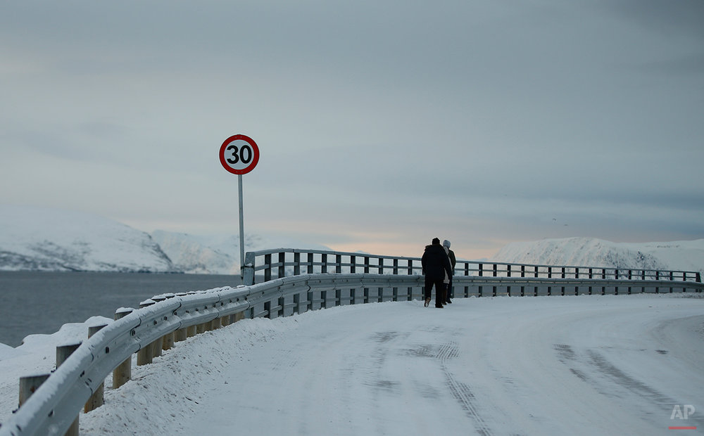 In this photo taken Thursday Feb. 4, 2016, asylum seekers make their way back to the refugee camp from the centre of Hammerfest, northern Norway. Waiting for their asylum claims to be processed, hundreds of people in emergency shelters in Hammerfest and neighboring towns are slowly getting used to the extreme climate and unfamiliar customs of the High North. (AP Photo/Alastair Grant)