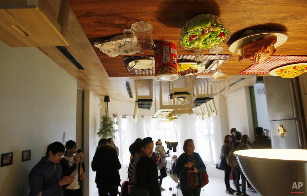 Visitors look around inside an upside-down house created by a group of Taiwanese architects at the Huashan Creative Park in Taipei, Taiwan, Tuesday, Feb. 23, 2016. With a build price of $600,000 and over 300 square meters (3,230 square feet) of floor space filled with real home furnishings, the upside-down house will continue to be on display to visitors until July 22. (AP Photo/Wally Santana)