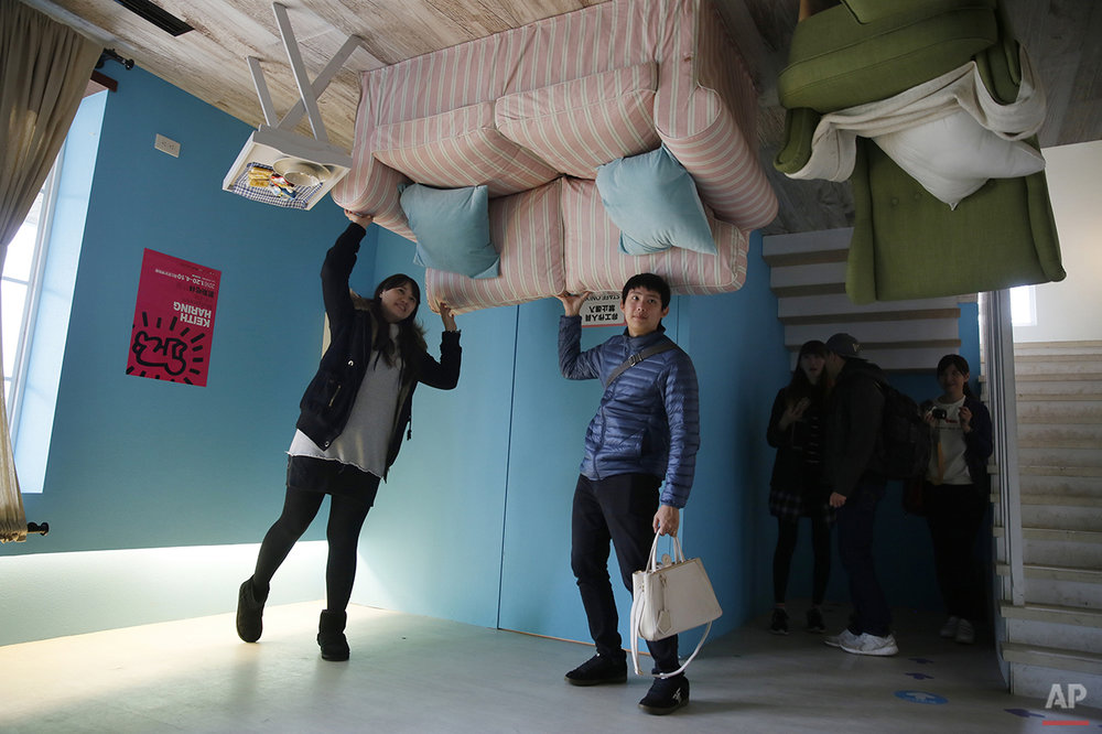 Visitors pose inside an upside-down house created by a group of Taiwanese architects at the Huashan Creative Park in Taipei, Taiwan, Tuesday, Feb. 23, 2016. With a build price of $600,000 and over 300 square meters (3,230 square feet) of floor space filled with real home furnishings, the upside-down house will continue to be on display to visitors until July 22. (AP Photo/Wally Santana)