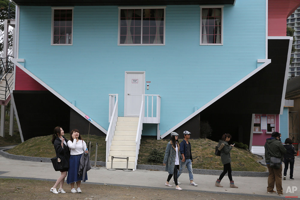 Visitors take photographs outside of an upside-down house at the Huashan Creative Park in Taipei, Taiwan, Tuesday, Feb. 23, 2016. With a build price of $600,000 and over 300 square meters (3,230 square feet) of floor space filled with real home furnishings, the upside-down house will continue to be on display to visitors until July 22. (AP Photo/Wally Santana)
