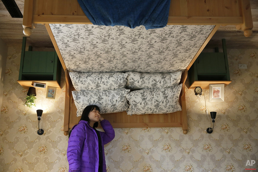 A visitor poses inside an upside-down house created by a group of Taiwanese architects at the Huashan Creative Park in Taipei, Taiwan, Tuesday, Feb. 23, 2016. With a build price of $600,000 and over 300 square meters (3,230 square feet) of floor space filled with real home furnishings, the upside-down house will continue to be on display to visitors until July 22. (AP Photo/Wally Santana)