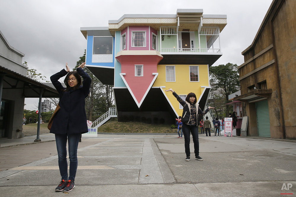Visitors pose outside of an upside-down house created by a group of Taiwanese architects at the Huashan Creative Park in Taipei, Taiwan, Tuesday, Feb. 23, 2016. With a build price of $600,000 and over 300 square meters (3,230 square feet) of floor space filled with real home furnishings, the upside-down house will continue to be on display to visitors until July 22. (AP Photo/Wally Santana)