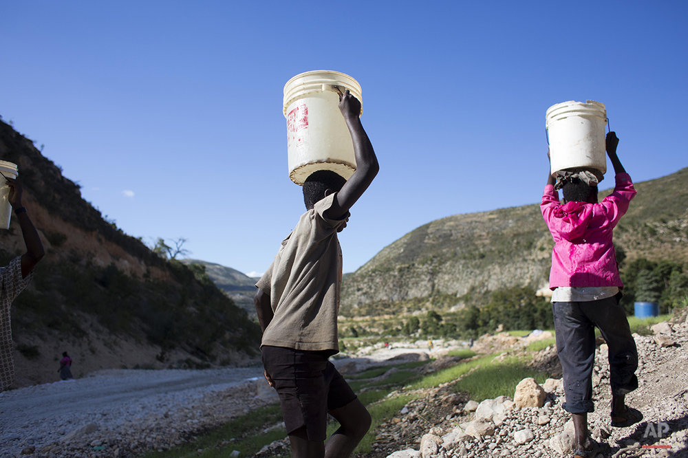 In this Feb. 15, 2016 photo, residents carry buckets filled with water they collected from the Soliette river, to irrigate their vegetable plots, in Fonds Verrettes, Haiti. Economist Kesner Pharel says local agricultural production has contracted so severely over the last two years that 70 percent of the crops consumed in Haiti are now imported, up from roughly 50 percent in the past. (AP Photo/Dieu Nalio Chery)