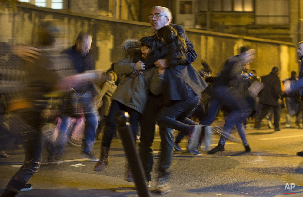 A man carries two children after panic broke out among mourners who payed their respect at the attack sites at restaurant Le Petit Cambodge (Little Cambodia) and the Carillon Hotel in Paris, Sunday, Nov. 15, 2015. Panic broke out as the crowd heard someone screaming from another location around the corner. Thousands of French troops deployed around Paris on Sunday and tourist sites stood shuttered in one of the most visited cities on Earth while investigators questioned the relatives of a suspected suicide bomber involved in the country's deadliest violence since World War II.