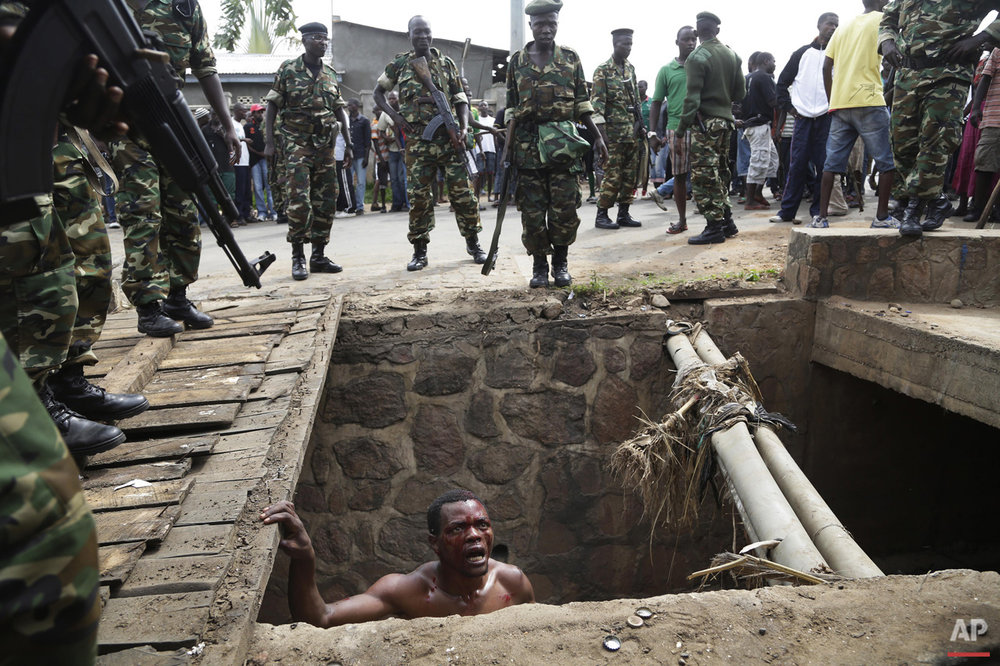 Jean Claude Niyonzima, a suspected member of the ruling party's Imbonerakure youth militia, pleads with soldiers to protect him from a mob of demonstrators after he emerged from hiding in a sewer in the Cibitoke district of Bujumbura, Burundi on Thursday May 7, 2015. Niyonzima said he fled from his house into a sewer under a hail of stones thrown by a mob protesting against President Pierre Nkurunziza's decision to seek a third term in office.