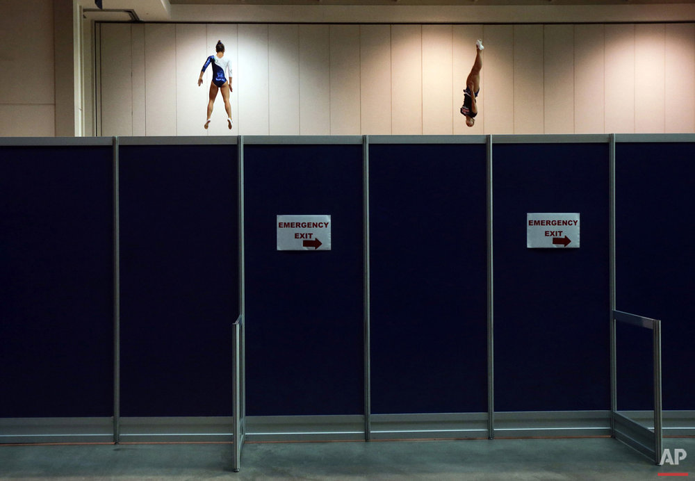 Brazil's Camilla Lopes, left, and the United States' Charlotte Drury warm up on trampolines behind a partition before women's trampoline competition at the Pan Am Games in Toronto, Sunday, July 19, 2015.