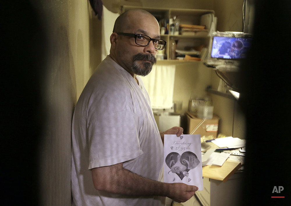 In this photo taken on Tuesday, Dec. 28, 2015, condemned inmate Robert Sarinana displays artwork he created in his cell on death row at San Quentin State Prison in San Quentin, Calif. (AP Photo/Ben Margot)