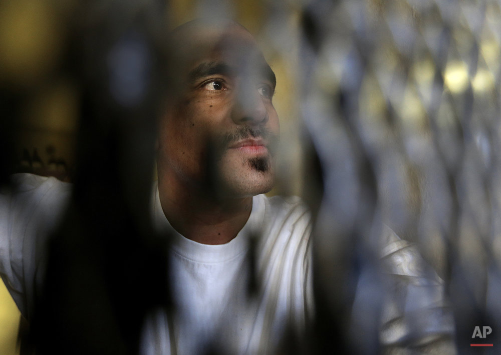 In this photo taken on Tuesday, Dec. 29, 2015, condemned inmate Martin Navarette peers out his cell on death row at San Quentin State Prison in San Quentin, Calif. With California's lethal injection protocol in limbo, the nearly 750 inmates at San Quentin State Prison, the nation's most populous death row, are more likely to die from natural causes or suicide than execution. The inmates await a final decision on a proposed one-drug execution method to replace a three-drug method that a federal judge invalidated in 2006 as a potentially cruel and unusual punishment. (AP Photo/Ben Margot)