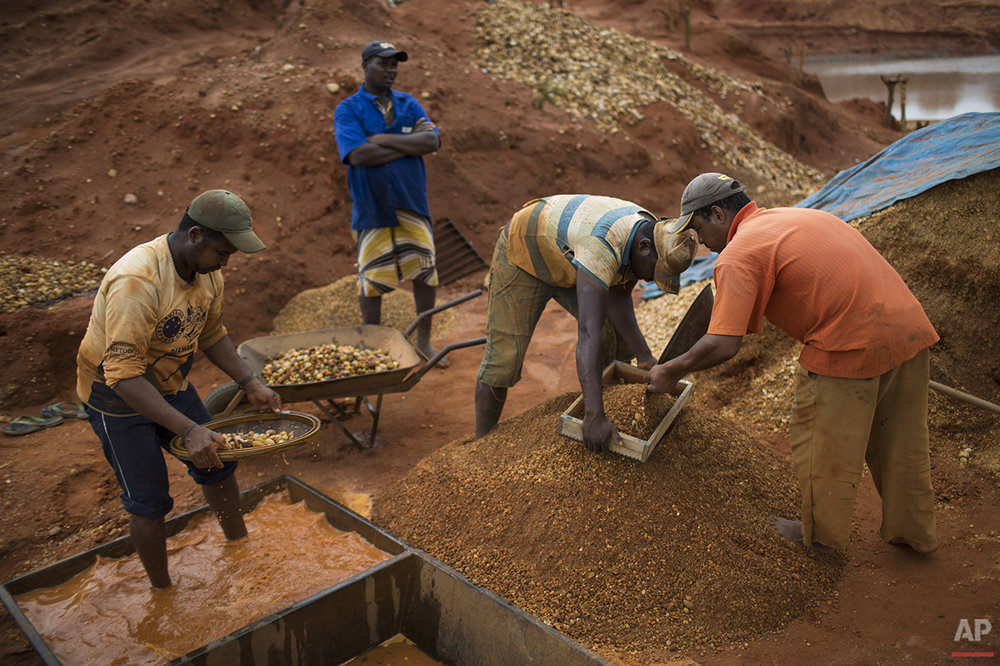 In this Nov. 17, 2015 photo, artisanal miners separate gravel with sieves as they search for diamonds at an abandoned mine in Areinha, Minas Gerais state, Brazil. During the weeks-long mining process, the group excavates the soil down to a layer of gravel of up to 50 meters (yards) deep. (AP Photo/Felipe Dana)