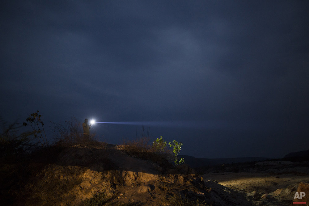 In this Nov. 15, 2015 photo, a man holding a flashlight searches for a cell signal atop a small hill in Areinha, Brazil. Far into the heart of Brazil's Minas Gerais state, artisanal miners explore the massive craters left behind by giant mining companies in search of diamonds. (AP Photo/Felipe Dana)