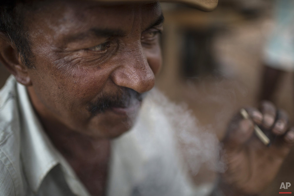 In this Nov. 15, 2015 photo, artisanal diamond miner Geraldo smokes in Areinha, Minas Gerais state, Brazil. Geraldo is one of hundreds of people across the region digging for diamonds, living in isolated wooden huts without electricity and with no stable income. (AP Photo/Felipe Dana)